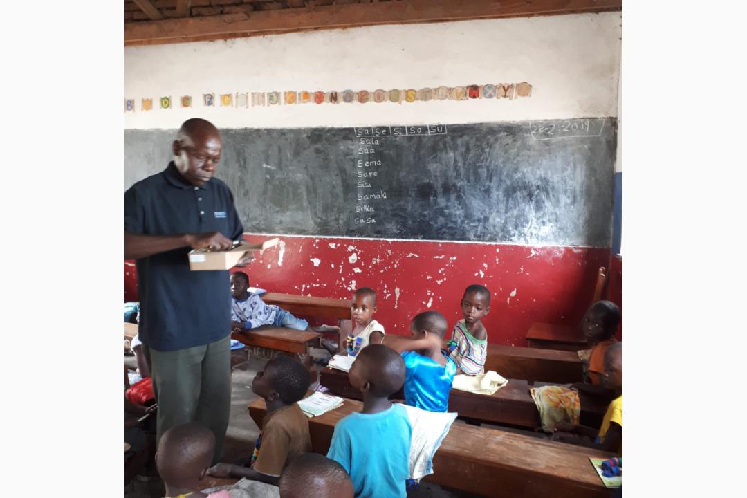 Lehrer-mit-seiner-Klasse-beim-Verteilen-der-Bleistifte