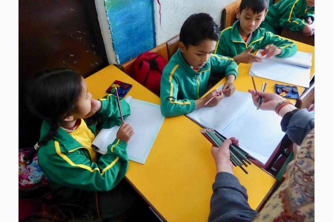 Verteilen-von-Bleistiften-an-Schulkinder